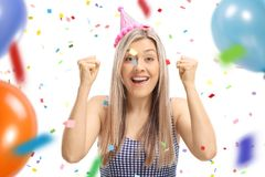 Young woman wearing a party hat gesturing happiness with confett. I streamers and balloons flying around her isolated on white background Stock Image