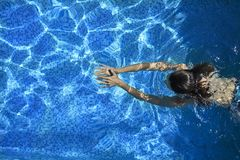 Woman swimming in the pool royalty free stock photography