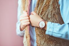 Young woman wearing pink gold wristwatch, brown sheepskin vest. And blue blouse. Standing in front of pastel pink wall royalty free stock photography