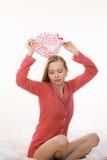 Young woman wearing pink pajamas putting bathing cap Stock Images