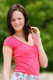 Young woman wearing a pink t shirt. Portrait of young woman wearing a pink t shirt with green tree background Stock Image