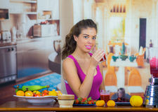 Young woman wearing pink top enjoying healthy breakfast, eating fruits, drinking smoothie and smiling, home kitchen. Background Royalty Free Stock Photography