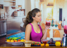 Young woman wearing pink top enjoying healthy breakfast, eating fruits, drinking smoothie and smiling, home kitchen. Background Stock Image