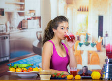 Young woman wearing pink top enjoying healthy breakfast, eating fruits, drinking smoothie and smiling, home kitchen. Background Royalty Free Stock Images