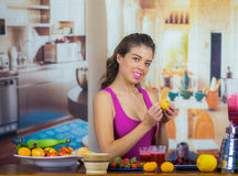 Young woman wearing pink top enjoying healthy breakfast, eating fruits, drinking smoothie and smiling, home kitchen. Background Stock Photo