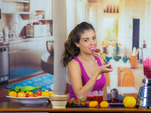 Young woman wearing pink top enjoying healthy breakfast, eating fruits, drinking smoothie and smiling, home kitchen. Background Royalty Free Stock Photos
