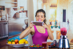 Young woman wearing pink top enjoying healthy breakfast, eating fruits, taking picture using mobile phone and smiling. Home kitchen background Stock Image