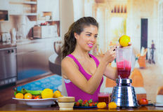Young woman wearing pink top enjoying healthy breakfast, eating fruits, using blender preparing smoothie and smiling. Home kitchen background Stock Image