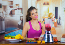 Young woman wearing pink top enjoying healthy breakfast, eating fruits, using blender preparing smoothie and smiling. Home kitchen background Stock Photos