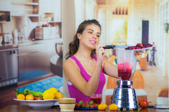Young woman wearing pink top enjoying healthy breakfast, eating fruits, using blender preparing smoothie and smiling. Home kitchen background Royalty Free Stock Photography