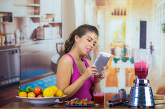 Young woman wearing pink top enjoying healthy breakfast, eating fruits, using blender preparing smoothie and smiling. Home kitchen background Stock Photo