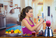 Young woman wearing pink top enjoying healthy breakfast, eating fruits, using blender preparing smoothie and smiling. Home kitchen background Stock Photography