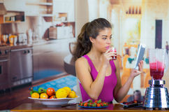 Young woman wearing pink top enjoying healthy breakfast, eating fruits, using blender preparing smoothie and smiling. Home kitchen background Royalty Free Stock Photos