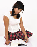 Young woman wearing plaid skirt reading a book Stock Images