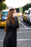 Young woman wearing protective mask and covering her mouth with her hand on the street in the city with air pollution Stock Photography