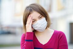 Young woman wearing a protective mask in public place. Safety during COVID-19 outbreak