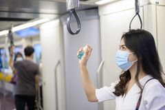 Young woman wearing protective mask in subway is using alcohol to wash hands, travel under Covid-19 pandemic, safety travels,