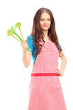 Young woman wearing red apron and holding plastic spoons Royalty Free Stock Photo