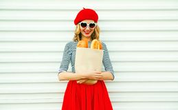 Young woman wearing red beret holding paper bag with a long white bread baguette. Happy smiling young woman wearing red beret holding paper bag with a long white stock image