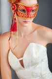 Young woman wearing red carnival mask Stock Images