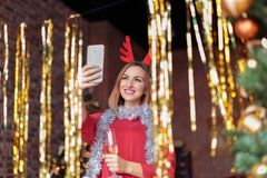 Young woman wearing red dress with antler deer headband taking selfie on Christmas party Stock Image