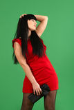 Young woman wearing red dress with emotions. Isolated on green background Royalty Free Stock Photo