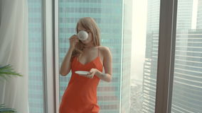 Young woman wearing red nightdress drinking cup of tea and standing near the window stock footage