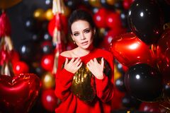Young woman wearing red sweater and black tights holding heart. Beautiful hot female posing in sensual way in St Royalty Free Stock Images