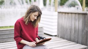 Young woman wearing red working with a tablet near a fountain stock video