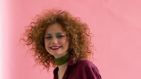 Young woman wearing a 70s retro clothes striking a pose in studio. Disco diva.  stock footage