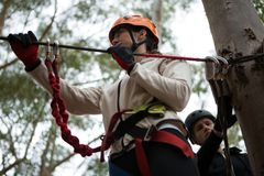 Young woman wearing safety helmet getting ready to cross zip line. In the forest royalty free stock photo