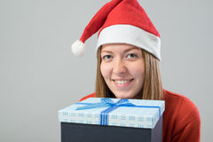 Young woman wearing a santa hat with gift box Stock Images
