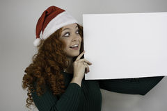 Young woman wearing Santa hat holding empty sign Stock Image