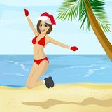 Young woman wearing santa hat jumping on tropical beach Royalty Free Stock Photo