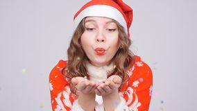 Young woman wearing Santa`s hat blowing away confetti. Beautiful young woman wearing Santa`s hat blowing away confetti stock video footage