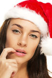 Young woman wearing santas hat put her fingertip t Stock Images