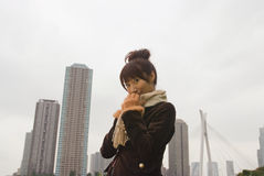 Young woman wearing scarf. Standing in front of high buildings Stock Images