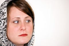 Young Woman Wearing Scarf is Worried and Concerned. This young Caucasian woman is wearing a gray patterned scarf and has a worried or concerned facial expression Stock Photography