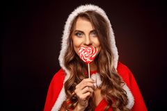 Christmas and New Year. Woman in santa costume with hood standing on black covering mouth with lollipop smiling. Young woman wearing santa costume with hood stock image