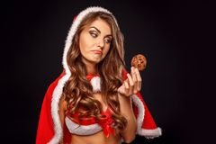 Christmas and New Year. Woman in santa costume standing isolated on black. Young woman wearing santa costume standing isolated on black wall stock photos