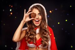 Christmas and New Year. Woman in santa costume standing isolated on black. Young woman wearing santa costume standing isolated on black wall stock images