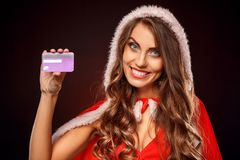 Christmas and New Year. Woman in santa costume standing isolated on black with credit card smiling cheerful close-up. Young woman wearing santa costume standing royalty free stock images