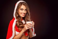 Christmas and New Year. Woman in santa costume standing isolated on black drinking hot tea smiling playful close-up. Young woman wearing santa costume standing stock images