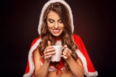 Christmas and New Year. Woman in santa costume standing isolated on black looking at hot coffee close-up. Young woman wearing santa costume standing isolated on stock photography
