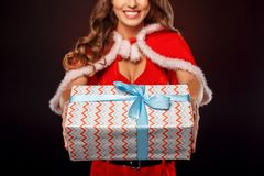 Christmas and New Year. Woman in santa costume standing isolated on black with present close-up smiling joyful. Young woman wearing santa costume standing stock photo
