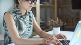 Young woman wearing smartwatch using laptop computer stock footage