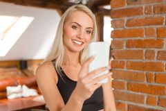 Young woman wearing sports clothes taking selfie using phone royalty free stock photo