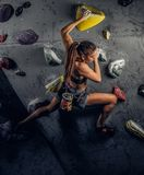 Young woman wearing sportswear practicing rock-climbing on a wall indoors. A young woman wearing sportswear practicing rock-climbing on a wall indoors stock images