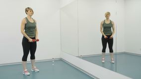 Woman training with dumbbells in hands in front of mirror. Young woman wearing sporty outfit is in the gym. Sporty young woman is in front of the mirror. Active stock video footage