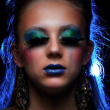 Young woman wearing strange make-up with tears Stock Photography